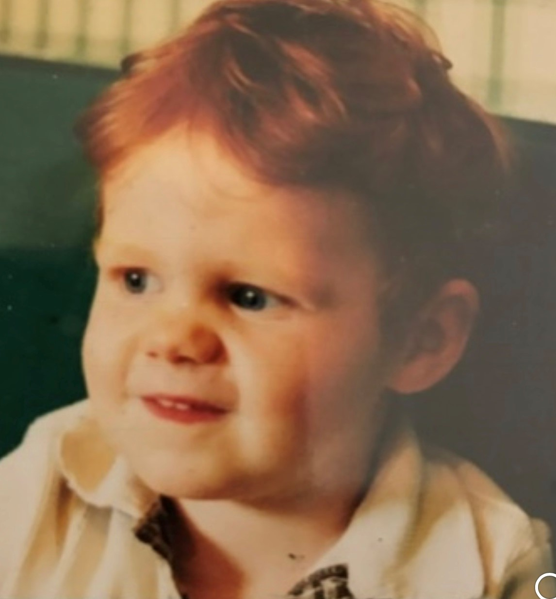 Muir as a toddler with bright red hair and a cheeky grin.