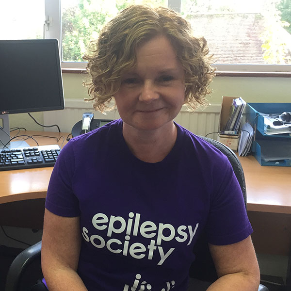 Andree Mayne has a blonde, curly bob. She is wearing a purple Epilepsy Society t-shirt and is smiling.