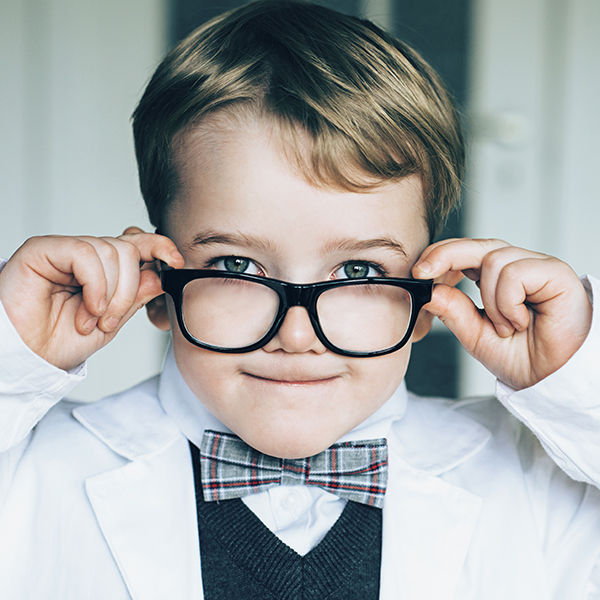 Young boy in science overall and bow tie, peering over top of large, black glasses