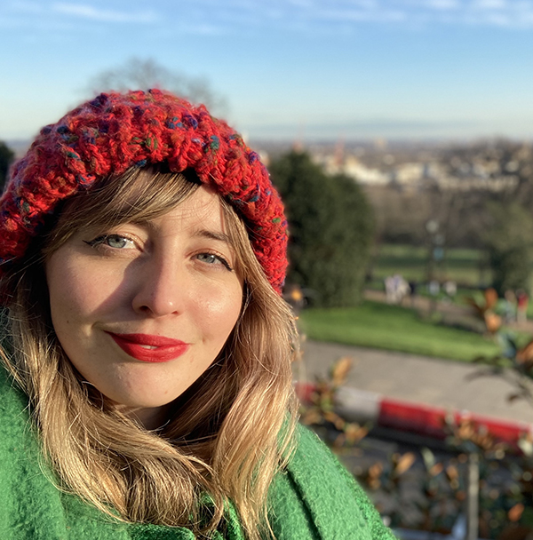 Martha has long blonde hair with her fringe swept to one side. She has bright red lipstick and is wearing a red woollen hat and a bright green coat.