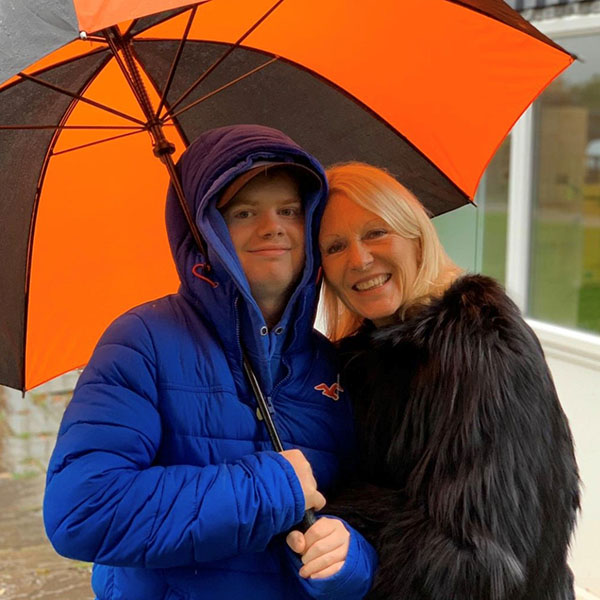 Muir Maxwell and his mum, Ann, sheltering under a bright orange and black striped umbrella