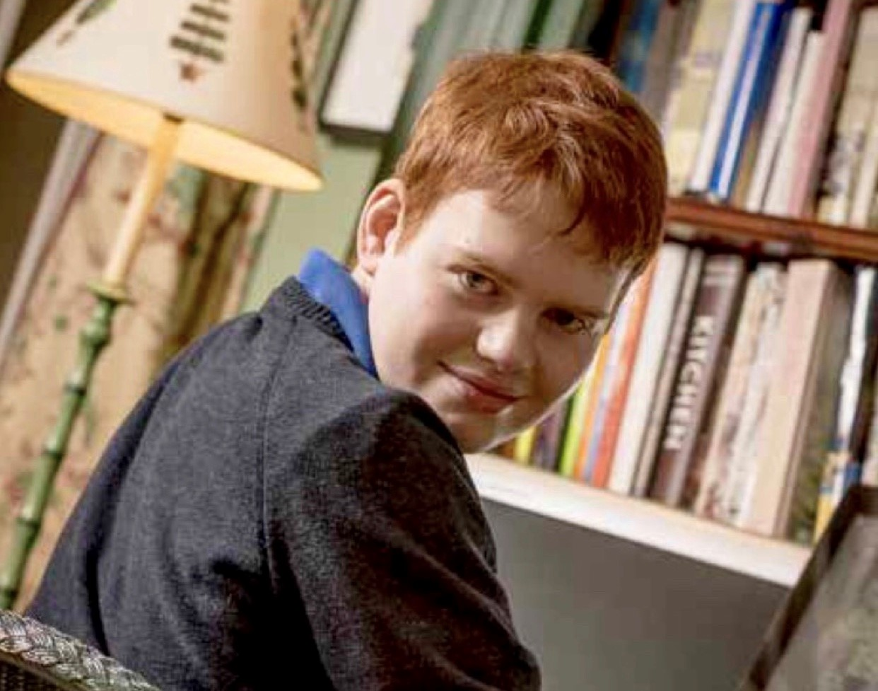Muir is in school uniform - a grey jumper - and is grinning over his right shoulder. He is sitting at a desk, in front of a bookcase.