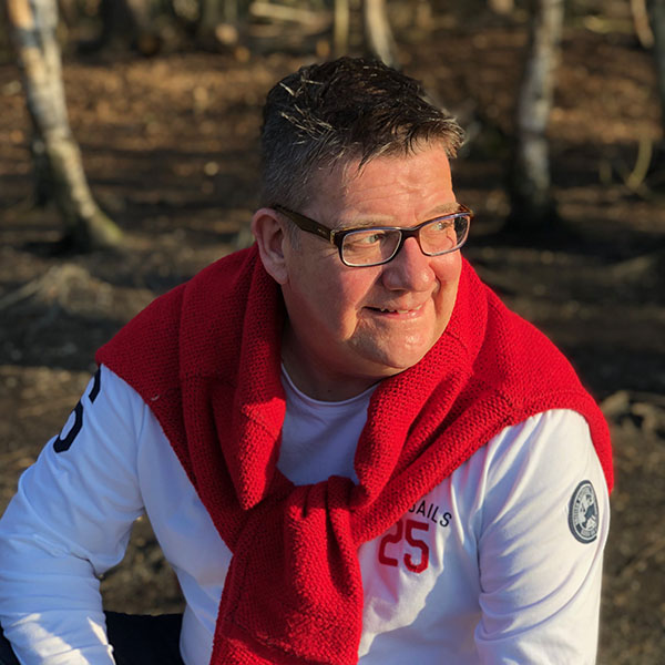 ​​​​Steve Turner is wearing a whilte sports shirt with a red jumper tied around his shoulders. He has spiky hair, glasses, a friendly smile and is looking off camera, over his right shoulder