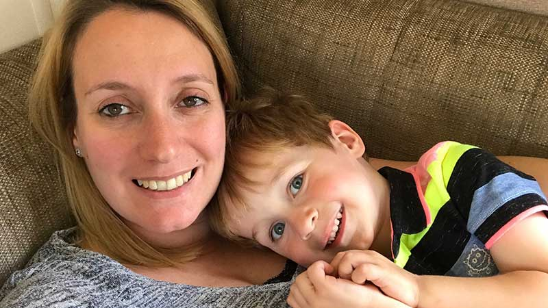 Woman and boy lying on a sofa smiling at the camera