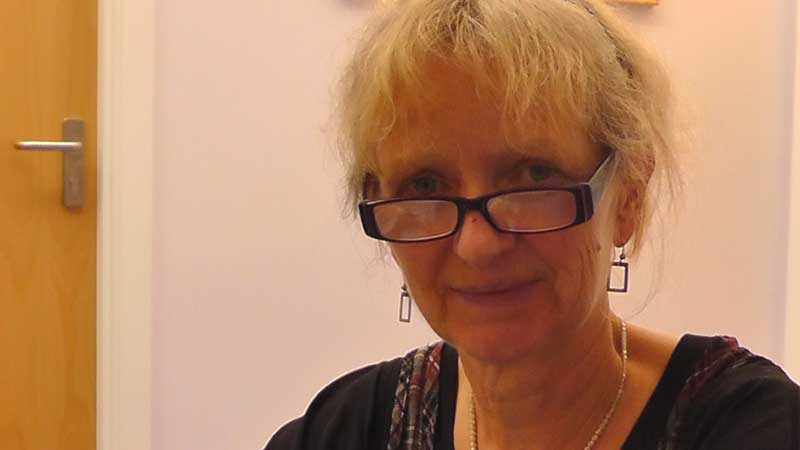 Woman wearing glasses smiling at the camera.