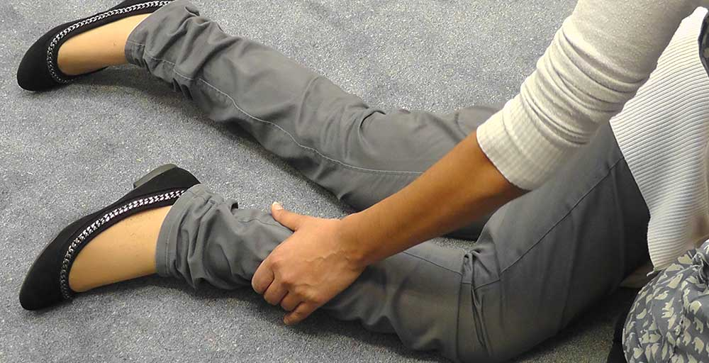 Move the bent leg that is nearest to you, in front of their body so that it is resting on the floor. This position will help to balance them.